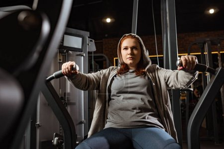 Photo pour Foyer sélectif de la fille en surpoids confiante faisant l'exercice d'extension des bras sur la machine de fitness - image libre de droit