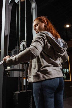 Photo pour Fille en surpoids en sweat à capuche gris faisant exercice d'extension des bras sur la machine de fitness - image libre de droit
