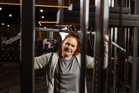 Photo for Selective focus of overweight girl doing arms extension exercise on training machine - Royalty Free Image