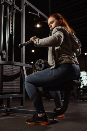 Photo for Low angle view of concentrated overweight girl doing arms extension exercise on fitness machine - Royalty Free Image