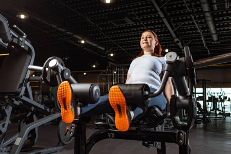 Photo for Purposeful overweight girl doing leg extension exercise on fitness machine - Royalty Free Image