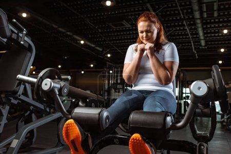 Photo pour Concentrée fille en surpoids faisant l'exercice d'extension de jambe sur la machine de fitness - image libre de droit