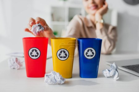 Photo for Cropped view of businesswoman throwing crumpled papers into recycling buckets  in office - Royalty Free Image