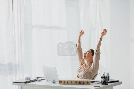 Photo pour Femme d'affaires souriante reposant sur le lieu de travail avec des papiers froissés, un ordinateur portable et des cubes alphabétiques avec un mot de bien-être - image libre de droit