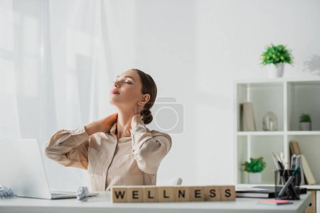 Photo for Attractive businesswoman relaxing at workplace with laptop and alphabet cubes with wellness word - Royalty Free Image