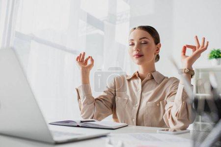 Photo pour Belle femme d'affaires méditant avec les yeux fermés et gyan mudra sur le lieu de travail avec ordinateur portable - image libre de droit
