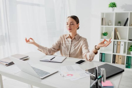 happy businesswoman meditating with closed eyes and gyan mudra at workplace with laptop and smartphone