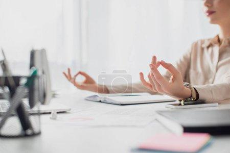Photo pour Vue recadrée de femme d'affaires méditant avec mudra gyan sur le lieu de travail avec bloc-notes - image libre de droit
