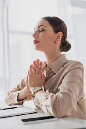 Photo pour Belle femme d'affaires méditant avec geste namaste et les yeux fermés au bureau - image libre de droit