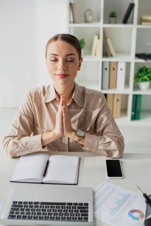Photo pour Belle femme d'affaires méditant avec geste namaste sur le lieu de travail avec ordinateur portable, smartphone et bloc-notes - image libre de droit