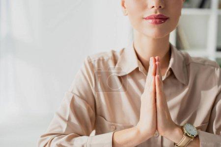 Photo pour Vue recadrée de femme d'affaires méditant avec geste namaste au bureau - image libre de droit