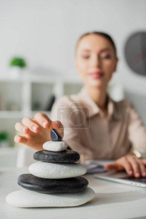 Photo pour Foyer sélectif de femme d'affaires travaillant avec un ordinateur portable sur le lieu de travail avec des pierres zen - image libre de droit
