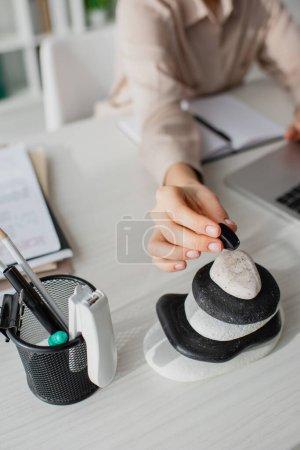 Photo pour Vue recadrée de femme d'affaires travaillant avec ordinateur portable sur le lieu de travail avec des pierres zen - image libre de droit