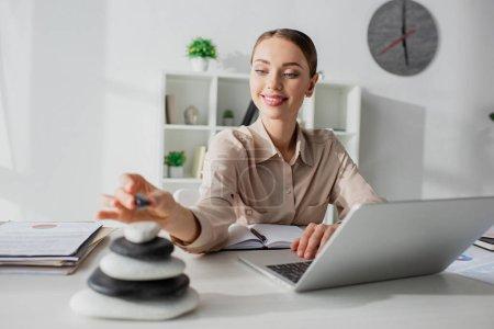 Photo pour Foyer sélectif de sourire femme d'affaires travaillant avec ordinateur portable sur le lieu de travail avec des pierres zen - image libre de droit