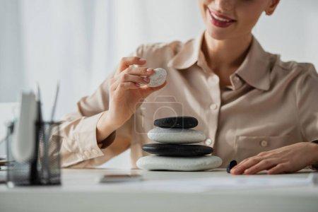 Photo pour Vue recadrée de femme d'affaires heureuse assise sur le lieu de travail avec des pierres zen - image libre de droit