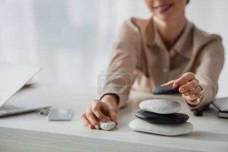 Photo pour Vue recadrée de femme d'affaires assise sur le lieu de travail avec des pierres zen, smartphone et ordinateur portable - image libre de droit