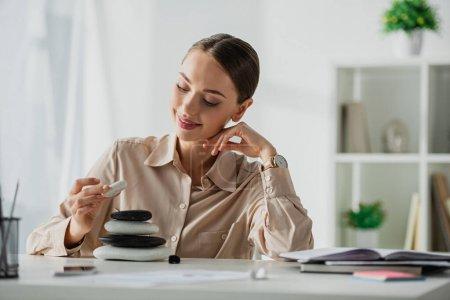 Photo pour Femme d'affaires heureuse assise sur le lieu de travail avec des pierres zen - image libre de droit