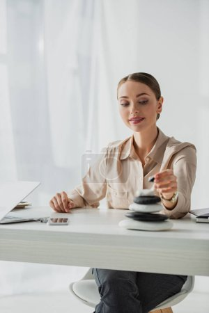 Photo pour Attrayant femme d'affaires assis sur le lieu de travail avec des pierres zen et ordinateur portable - image libre de droit