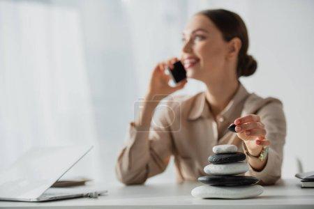 Photo pour Foyer sélectif de femme d'affaires parlant sur smartphone sur le lieu de travail avec des pierres zen - image libre de droit