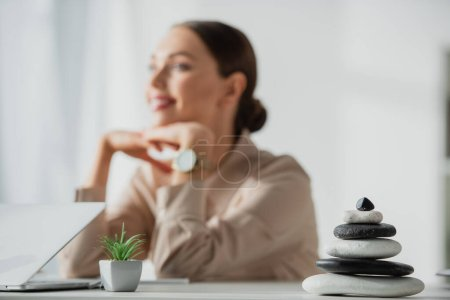 dreamy businesswoman sitting at workplace with plant, zen stones and laptop