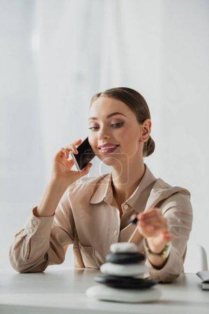 Photo pour Femme d'affaires heureuse parlant sur smartphone sur le lieu de travail avec des pierres zen - image libre de droit