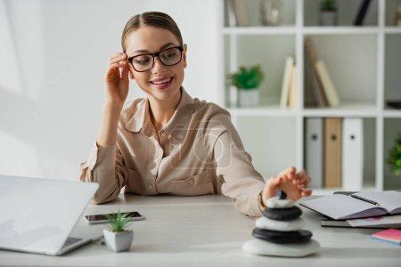Photo pour Femme d'affaires souriante assise sur le lieu de travail avec pierres zen, smartphone et ordinateur portable - image libre de droit