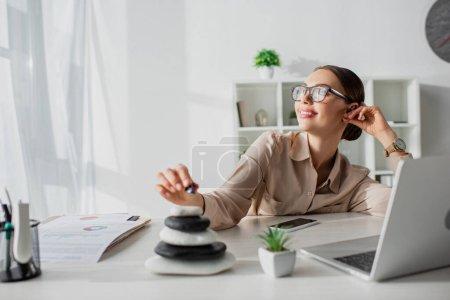 Photo pour Femme d'affaires rêveuse assis sur le lieu de travail avec des pierres zen et ordinateur portable - image libre de droit