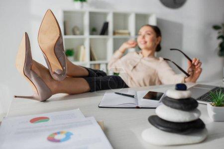 Photo pour Foyer sélectif de femme d'affaires assis avec les pieds sur la table avec des pierres zen dans le bureau - image libre de droit