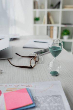 Photo pour Foyer sélectif de l'horloge de sable, lunettes, smartphone et ordinateur portable sur la table dans le bureau moderne - image libre de droit