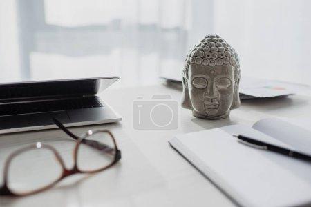 Photo pour Bouddha tête, lunettes, bloc-notes et ordinateur portable sur la table à l'espace de travail - image libre de droit