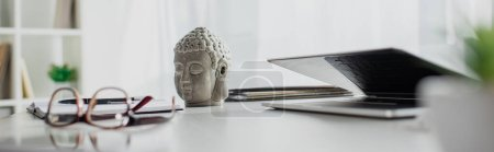 Photo pour Photo panoramique de la tête de Bouddha, des lunettes et de l'ordinateur portable sur la table dans un bureau moderne - image libre de droit