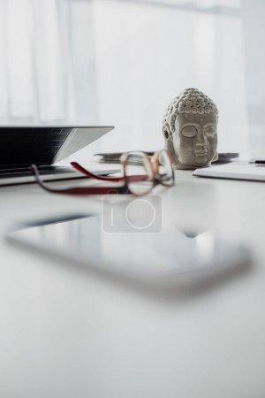 Photo pour Focalisation sélective de la tête de Bouddha, lunettes et ordinateur portable sur la table dans le bureau moderne - image libre de droit