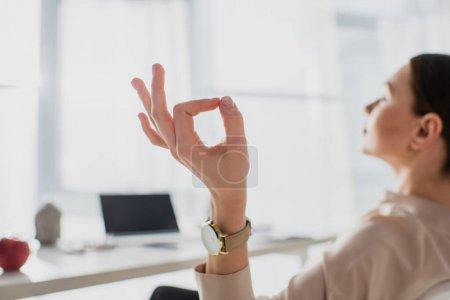 Photo pour Foyer sélectif de femme d'affaires méditant avec gyan mudra sur le lieu de travail - image libre de droit