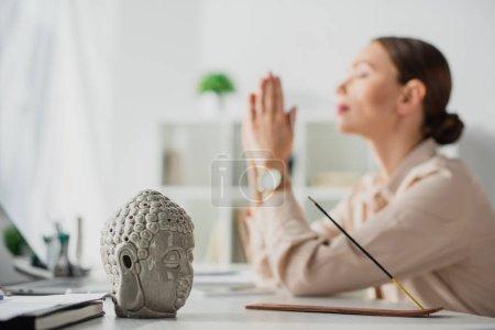 Photo pour Foyer sélectif de femme d'affaires méditant avec geste namaste sur le lieu de travail avec tête de Bouddha et bâton d'encens - image libre de droit