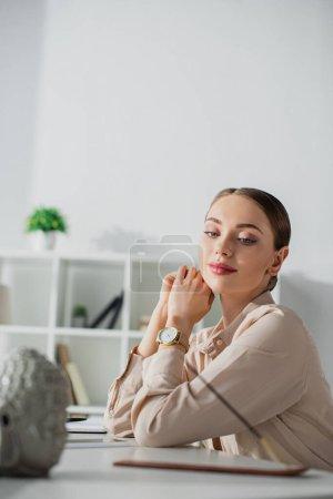 Photo pour Femme d'affaires assise au bureau avec tête de Bouddha et bâton d'encens - image libre de droit