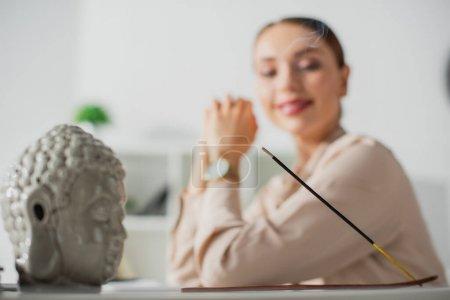 Photo pour Foyer sélectif de femme d'affaires heureuse assise dans le bureau avec tête de Bouddha et bâton d'encens - image libre de droit
