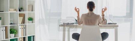 Photo pour Plan panoramique de femme d'affaires méditant dans la pose de lotus avec mudra gyan sur le lieu de travail avec bâton d'encens - image libre de droit