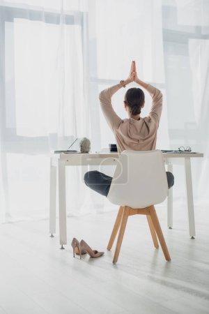 Photo pour Vue arrière de la femme d'affaires méditant avec geste namaste sur le lieu de travail avec bâton d'encens - image libre de droit