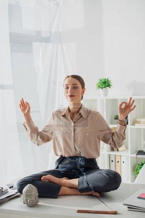 Photo pour Une femme d'affaires méditante en pose de lotus avec une mudra de gymnastique sur le lieu de travail avec une tête de Bouddha et un bâton d'encens - image libre de droit