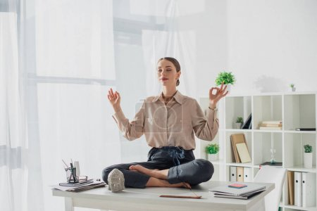 Photo pour Attractive business woman meditating in lotus pose with gyan mudra at workplace with Buddha head and incense stick - image libre de droit