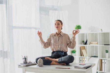 Photo pour Attrayant femme d'affaires méditant dans la pose de lotus avec mudra gyan sur le lieu de travail avec tête de Bouddha et bâton d'encens - image libre de droit
