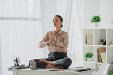 Photo pour Femme d'affaires entreprise méditant dans la pose de lotus avec geste namaste sur le lieu de travail avec tête de Bouddha et bâton d'encens - image libre de droit