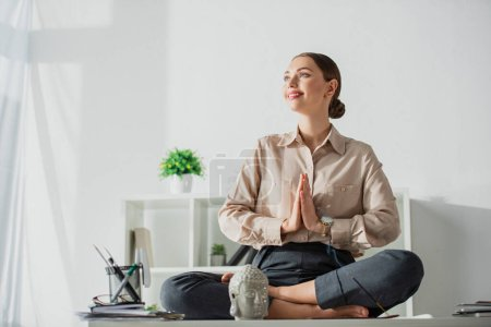 Photo pour Une femme d'affaires heureuse méditant en pose de lotus avec un geste de namaste sur le lieu de travail avec une tête de Bouddha et un bâton d'encens - image libre de droit