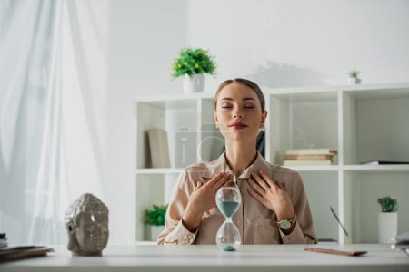 attractive tired businesswoman sitting at workplace with sand clock and buddha head