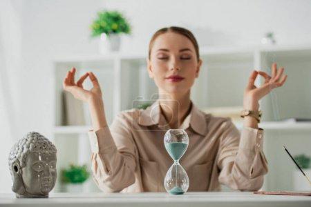 Photo pour Focalisation sélective d'une femme d'affaires méditant avec les yeux fermés et mudra gynécologique sur le lieu de travail avec tête de Bouddha, horloge à sable et bâton d'encens - image libre de droit