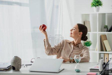 Photo pour Belle femme d'affaires souriante tenant pomme sur le lieu de travail avec tête de Bouddha, ordinateur portable et horloge de sable au bureau - image libre de droit