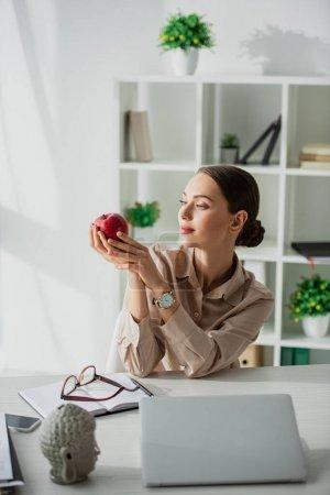 Photo pour Belle femme d'affaires tenant pomme sur le lieu de travail avec tête de Bouddha et ordinateur portable au bureau - image libre de droit