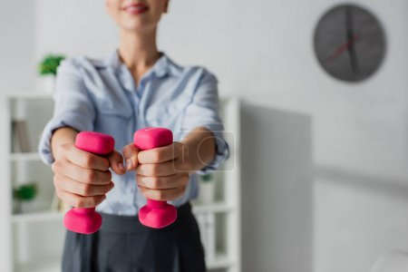 Photo for Cropped view of businesswoman training with pink dumbbells in office - Royalty Free Image