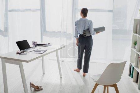 Photo pour Vue arrière de la jeune femme d'affaires tenant tapis de yoga à l'espace de travail avec ordinateur portable - image libre de droit