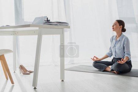 Photo pour Jeune femme d'affaires pratiquant le yoga en position lotus avec mudra gyan sur tapis au bureau - image libre de droit